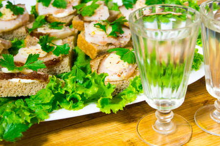 Traditional snack for Russian and Ukrainian people on the holidays. A sandwich with bacon, garlic and parsley under the glass of genuine Russian vodka