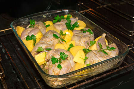 Cooking meat quails in the oven. Whole quail marinovani in spices with onions and mustard. Garnish with fresh potatoes and parsley