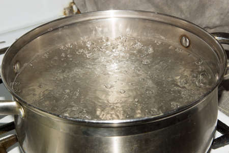 Stainless steel pot is on a gas stove and it boils water. Banco de Imagens - 88236766
