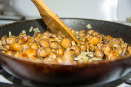 Small mushrooms fried in a pan as a whole. Fried mushrooms with onions.