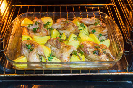 Quail meat. Freshly cooked quail with a side dish of new potatoes and parsley.