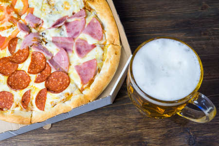Light beer in glass and fragrant Italian pizza.
