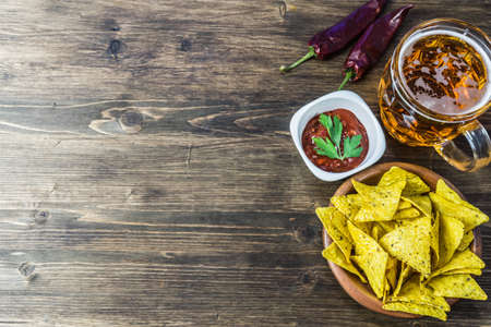 Nachos corn chips with classic tomato salsa. Fresh cold beer is perfect with savory snacks.
