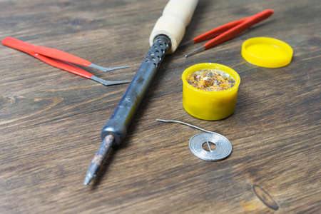 soldering iron with soldering accessories on a wooden background.