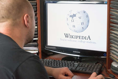 Belgorod, Russia - December 11, 2017: The man is Wikipedia. A white man sitting at the computer. On the monitor before his eyes opened the Wikipedia page ..