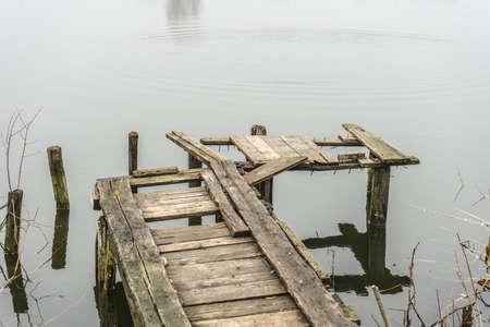 Old wooden bridge for fishing. The rotten bridge. Banco de Imagens
