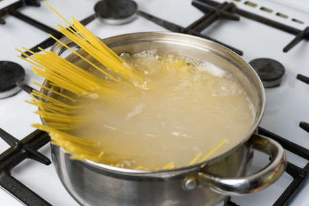Spaghetti cooked in boiling water on a gas stove. The traditional Italian food. 스톡 콘텐츠
