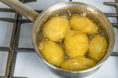 Le patate non trattate bollono in una pentola su un fornello a gas. Archivio Fotografico - 95477691