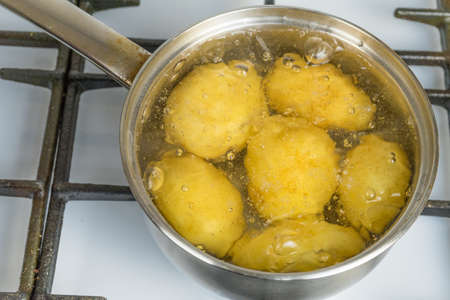 Untreated potatoes boil in a pot on a gas stove.