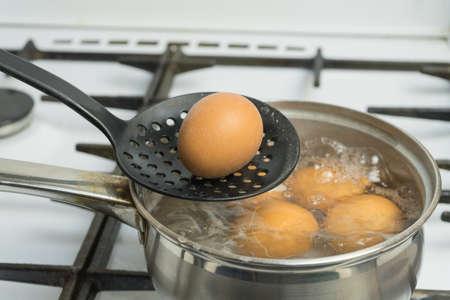 Les ?ufs de poule bouillent dans l'eau. Casserole avec le produit sur une cuisinière à gaz.