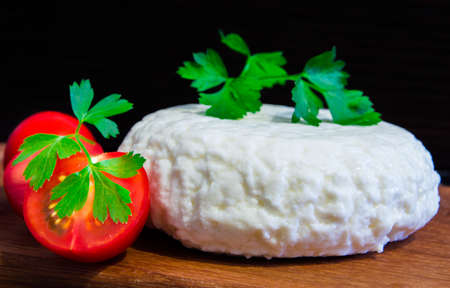 Fresh cheese with excellent taste and aroma. Cheese on wooden cutting Board with tomatoes and fresh herbs...