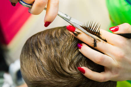 The hairdresser cuts the child. Haircut close-up... Stock Photo