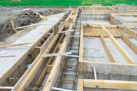 Production of the concrete base under the house with use of a removable timbering. Stock Photo