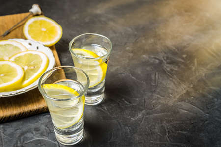 Glass of vodka. And lemon slicing on a plate. Place for your text. Stock fotó