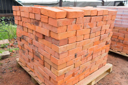 The bricks are stacked on wooden pallets and prepared for sale. Clay brick is an ecological building material. Banco de Imagens