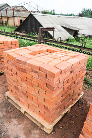 The bricks are stacked on wooden pallets and prepared for sale. Clay brick is an ecological building material. Imagens
