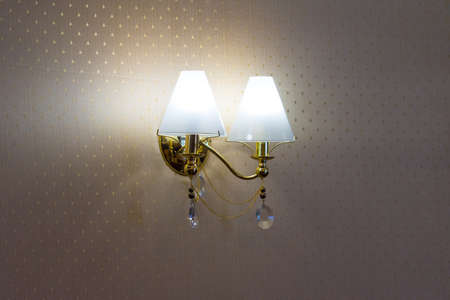 sconces hanging on the wall upholstered in fabric.. Banco de Imagens
