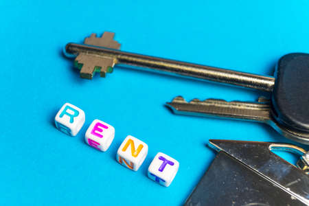 Inscription rent written colored cubes. Photo on the background of a key FOB in the shape of a house.. Banco de Imagens - 119883173