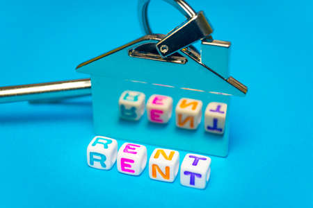 Inscription rent written colored cubes. Photo on the background of a key FOB in the shape of a house..