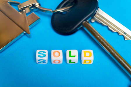 Keys with a keychain form the house and the inscription on the sale..