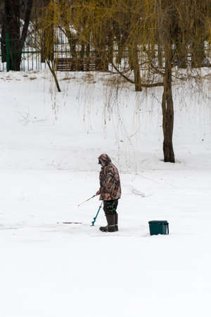 Fisherman in the winter on the ice fishing Banco de Imagens
