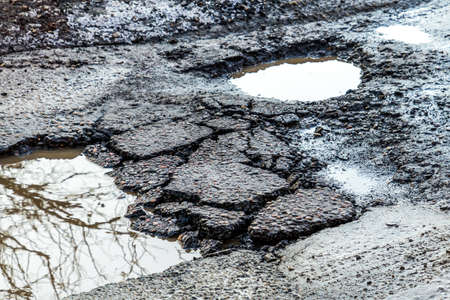 The hole in the road. Asphalt with defects. Dangerous encounter on the road. The hole in the road. Asphalt with defects. Dangerous encounter on the road.