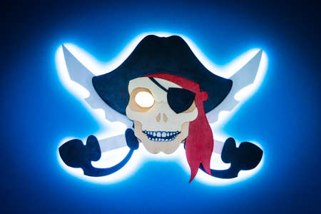 Photo pirate sign with neon lights on the blue wall Photo pirate sign with neon lights on the blue wall