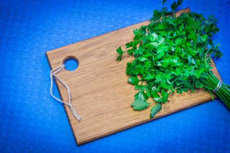 Fresh parsley is on the kitchen Board. Fresh parsley is on the kitchen Board. Banco de Imagens