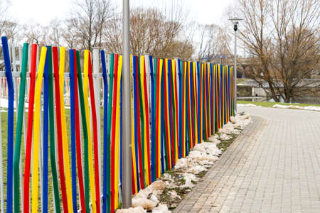 colorful fence. Fence made of metal painted in different colors. ccolorful fence. Fence made of metal painted in different colors. Banco de Imagens - 119882762