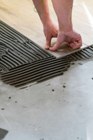 Laying tiles on the floor with a special glue. Laying tiles on the floor with a special glue. Banco de Imagens