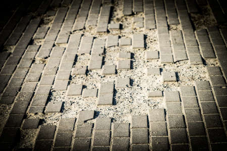 Pits on the sidewalk tiles. Place for your text. Pits on the sidewalk tiles. Place for your text. Banco de Imagens