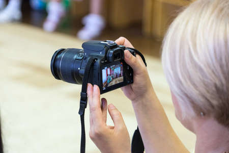 A woman takes pictures with a SLR camera. A woman takes pictures with a SLR camera. Banco de Imagens - 125355703