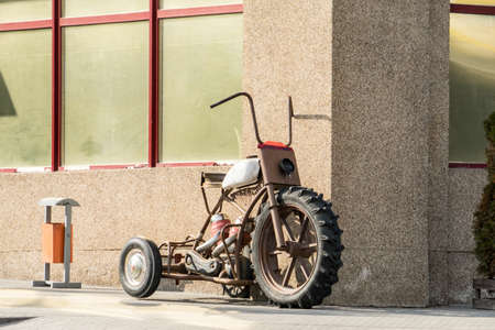 An old motorcycle stands against the wall. An old motorcycle stands against the wall.