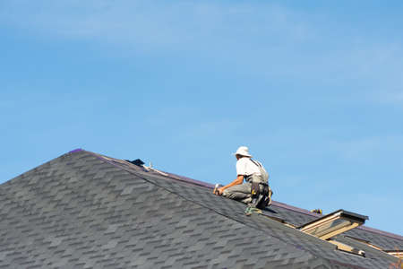 The man on the roof. Photo of a worker repairing the roof of the house. Banco de Imagens - 134526123