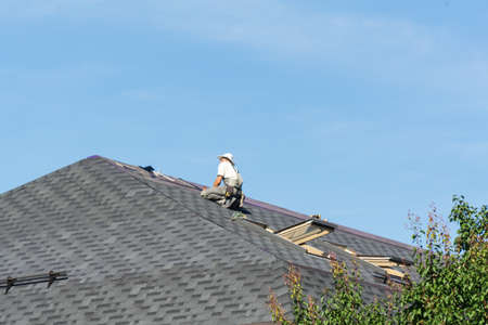 The man on the roof. Photo of a worker repairing the roof of the house.