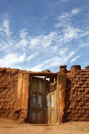 adobe wall: marrone adobe muro unexisting di una casa e un vecchio porta di legno nella citt� di Alamos, nel nord dello Stato di Sonora, Messico, America Latina
