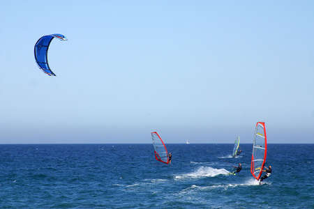 windsurfers and kite surfers enjoying the wind at the beach of the city of Barcelona, Catalunya, Spain, Europe