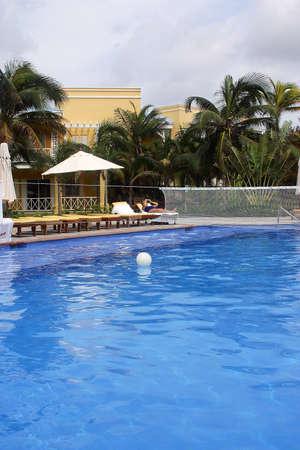 riviera maya: piscina con sillas de playa y parte de un hotel con detalles como la hacienda en Canc�n, Riviera Maya, Quinatan Roo, Mexico, Am�rica Latina  Foto de archivo