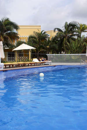 swimming pool with beach chairs and part of a hotel with hacienda like details in Cancun, Riviera Maya, Quinatan Roo, Mexico, Latin America photo