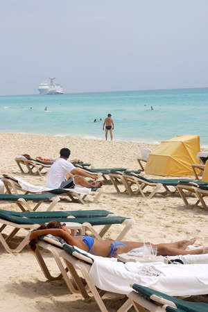 people taking the sun at the beach with a cruiser behind  in Cancun, Riviera Maya, Quinatan Roo, Mexico, Latin America photo