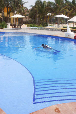riviera maya: person practicing diving with tank in a swimming pool of a hotel with hacienda like details in Cancun, Riviera Maya, Quinatan Roo, Mexico, Latin America Stock Photo