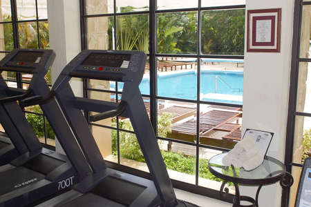 gym with look out to the swimming pool of a hotel with hacienda like details in Cancun, Riviera Maya, Quinatan Roo, Mexico, Latin America Imagens