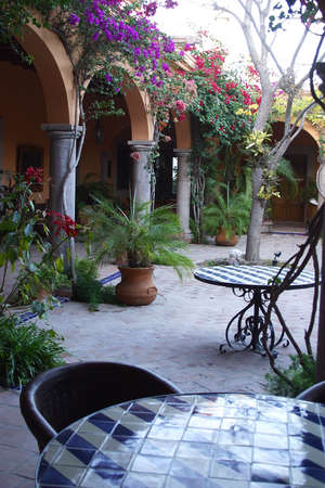 view of the arch way and inner patio with garden furniture  in a colonial house  of the town of Alamos, in the northern state of Sonora, Mexico, Latin America