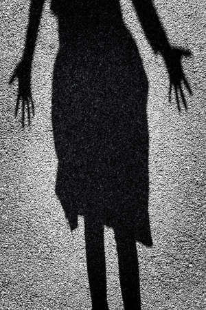 Mysterious shadow of a female figure standing in a doorway photo