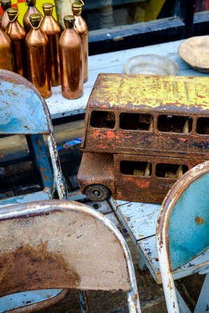 antiques: Collectible antiques for sale at Portobello Market, London, UK in a close up view of a rusted toy bus on old chairs