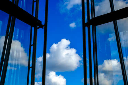 windows frame: Silhouette of open windows or building frame facing scattered white clouds over blue sky with copy space