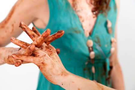 close-up of two women twisting their chocolate dirtied fingers