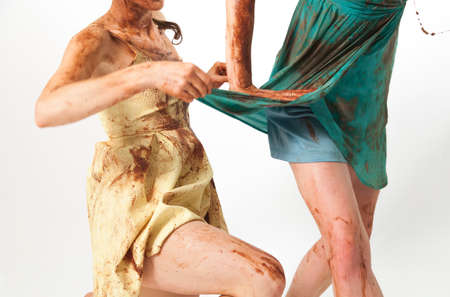 dirtied: Concept photo of girlfriend pulling other girls dress dirtied in chocolate