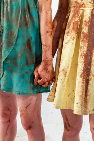 dirtied: Close-up of two unrecognizable women in bright dresses dirtied in chocolate holding hand in hand
