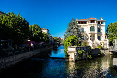 LIsle-sur-la-Sorgue, France - July 18, 2016: Brightly colored awnings of outdoor cafes line the edges of the Sorgue River in the heart of LIsle-sur-la-Sorgue, Provence Editorial
